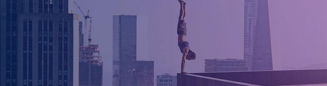 Person doing a handstand on edge of tall building